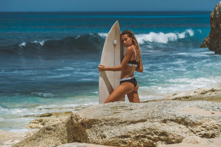 girl holding surfboard and watching to camera from her shoulder, low-angle shot