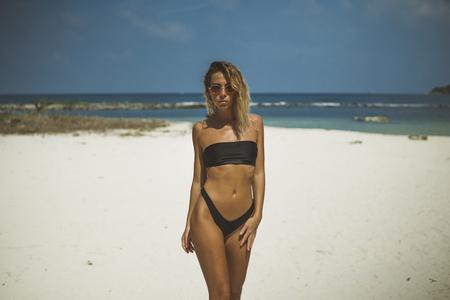 thin adult girl in black bikini and sunglasses walks along the white sand beach,
