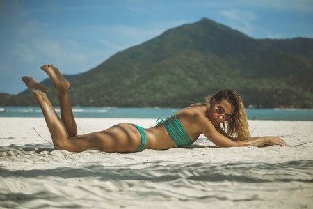 model with chic body sunbathing on white sand lying on her stomach, legs lifted, 스톡 콘텐츠