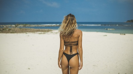 slender blonde with wavy hair poses with her back on the sand beach by ocean,