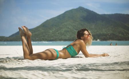 model with impressive body lying in sun on sand, legs lifted, eyes are closed 스톡 콘텐츠