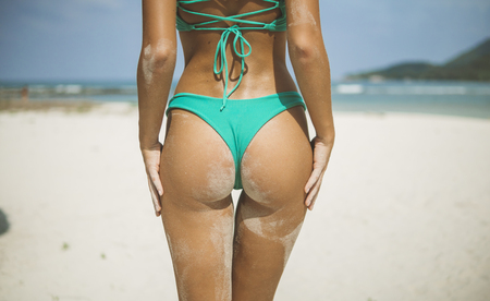 closeup of awesome back in blue bikini all in sand, girl stood from white sand 스톡 콘텐츠