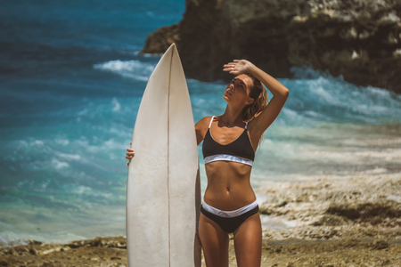 surfer girl standing with board on stone on ocean beach, looks covering her eyes 스톡 콘텐츠