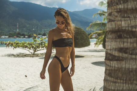 portrait of young blonde wearing sunglasses and black bikini posing at palm