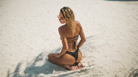 great view from the top model in bikini sitting on his knees on the white sand,