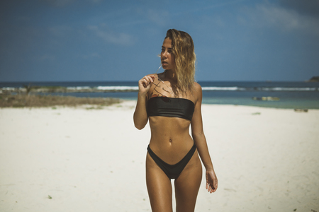 pretty slim young woman stands on tropical sand beach, keeps glasses in her hand 스톡 콘텐츠