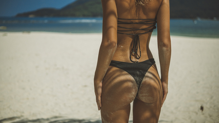 closeup nice back shot of girl with her butt in sand standing on white beach 스톡 콘텐츠