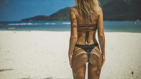 amazing back shot of bikini girl stands on white sand beach, her butt in sand