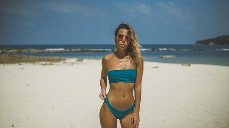 portrait of a beautiful suntanned young woman in blue bathing suit on beach sand
