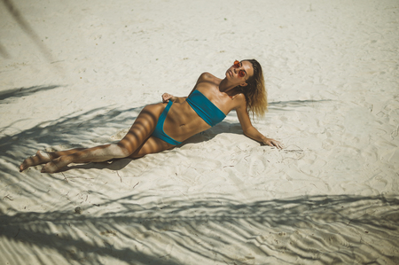 portrait of beautiful young blonde in blue bikini and glasses lying white sand 스톡 콘텐츠