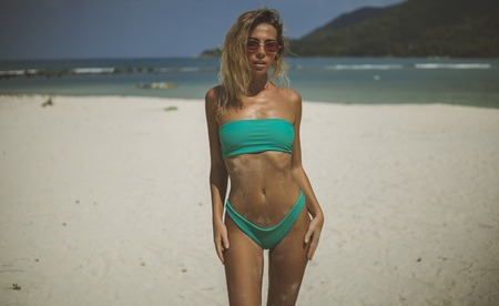 slim tanned girl in turquois bikini and sunglasses poses on the white sand beach