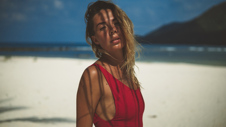 close up portrait of fair-haired girl in red swimsuit posing under palm tree 스톡 콘텐츠