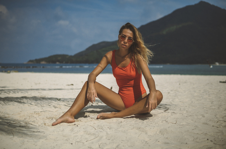 tropical beach with white sand, slim young woman in an orange swimsuit on coast