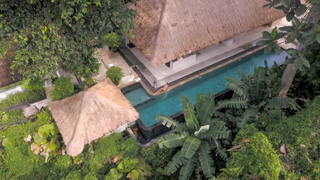 arial shoot of luxury bungalow villa located in jungles with blue swimming pool and model 스톡 콘텐츠