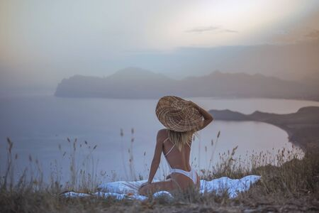 woman in hat on the blanket against of landscape during sunset 스톡 콘텐츠 - 132086135