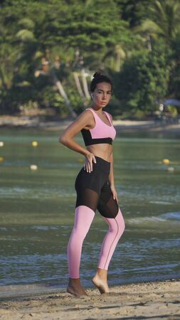 tanned sporty girl in pink yoga pants on sunny beach, beautiful day in tropics