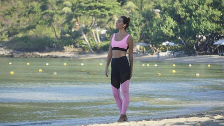 beautiful brunette in pink top stands isolated amid tropical forest near ocean,