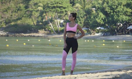 pretty brunette in pink top stands in beautiful pose on sunny beach by the water