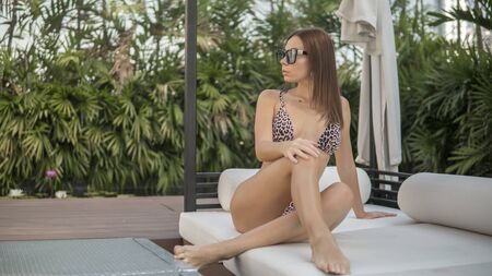 cute young brunette in catchy leopard bikini and sunglasses is sitting outdoors 版權商用圖片