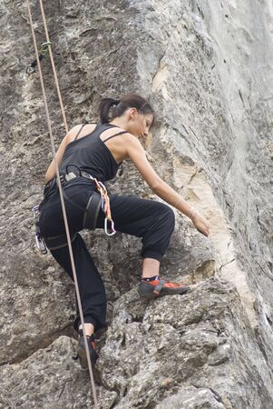 concentrate: Young woman climbing and stretching and nearly at the summit, on a rock face