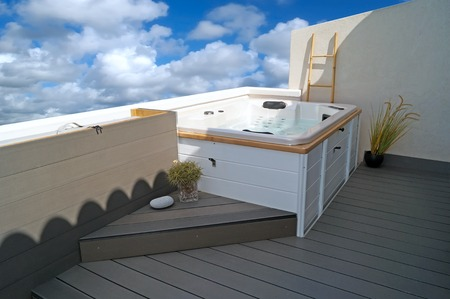 White Jacuzzi on wood plastic composite (WPC) integrated grey terrace.