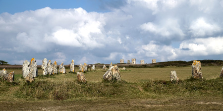 Alignment of megaliths in field with stone tower in background, in Camaret-sur-mer (France-Brittany)