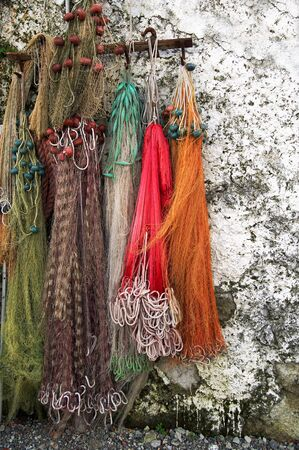 laid: Few colored fishing nets laid outdoor on a white wall