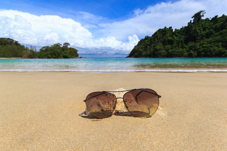 a bathing place: Close up dark glasses on the beach and blue sky background for summer time Stock Photo