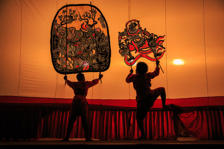 shadow puppets: RATCHABURI, THAILAND - APRIL 18: Large Shadow Play is performed at Wat Khanon on April 18, 2015. The ancient performing art involves manipulating puppets of cowhide in front of a backlit white