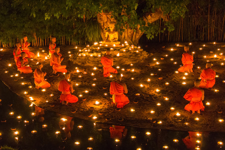 CHIANG MAI, THAILAND - JULY 11: Unidentified Thai monks meditate around buddha statue among many lanterns at Phan Tao temple in Asalha Puja Day on July 11, 2014 in Chiang Mai, Thailand.