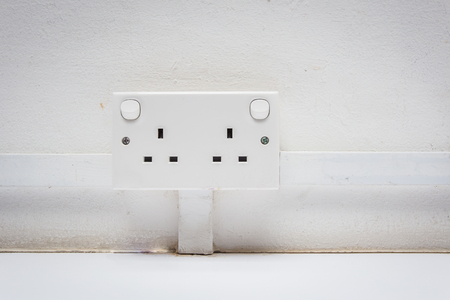 Universal electric socket adapter on white old wall. Stock Photo