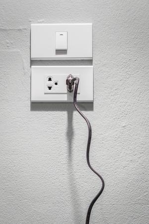 plugged in': Black plug plugged in a socket.