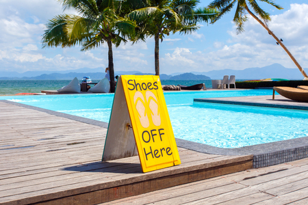 prohibits: No shoes label nearly pool - An iconic sign prohibits the use of no shoes.
