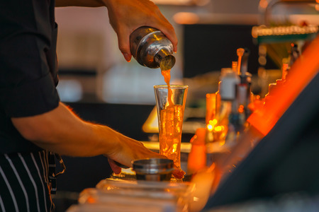 bartenders: Close up left hand bartenders in process of preparing orange juice for customers who order from rooftop bar and restaurant.