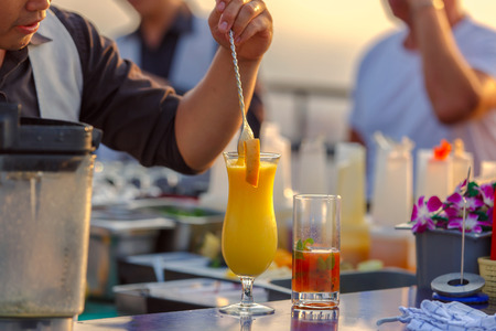 bebidas frias: Close up bartenders in process of preparing mix orange juice for customers who order from rooftop bar and restaurant. Foto de archivo