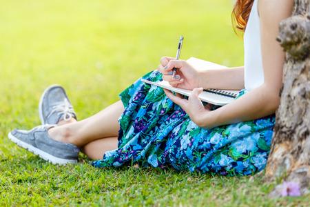 manos femeninas con pluma escribiendo en el cuaderno en el césped fuera Foto de archivo