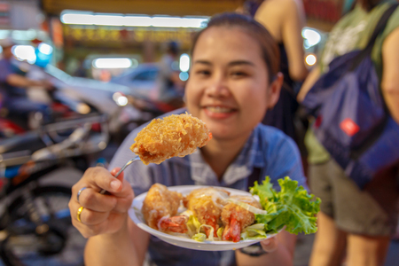 fritter: Asian women enjoy eating at fried prawn balls, shrimp fritter with lemon and cabbage slice a fork in her hand. select focus in fried prawn balls