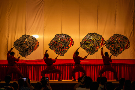 shadow puppets: RATCHABURI, THAILAND - MARCH 20: Large Shadow Play is performed at Wat Khanon on March 20, 2016. The ancient performing art involves manipulating puppets of cowhide in front of a backlit white Editorial