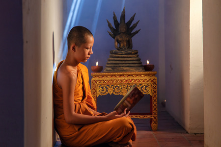 tantric: Young Novice monk reading a book at Ayutthaya historical park in Thailand