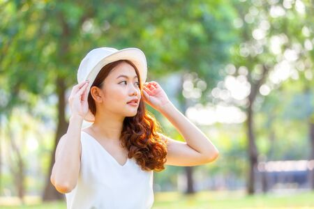 babyface: Portrait of pretty cheerful woman wearing white dress and straw hat in sunny warm weather day. Walking at summer park and smiling Stock Photo