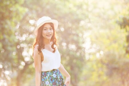 Portrait of pretty cheerful woman wearing white dress and straw hat in sunny warm weather day. Stock Photo