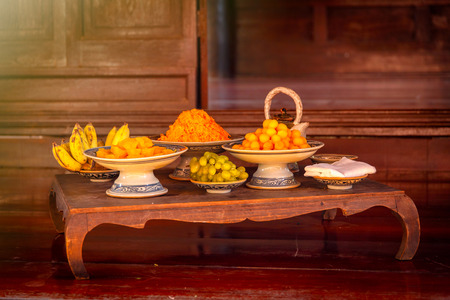 favorite colour: Many thai desserts (khanom wan thai) and fruits on the old wood table. Fractal on the earthenware is generic print