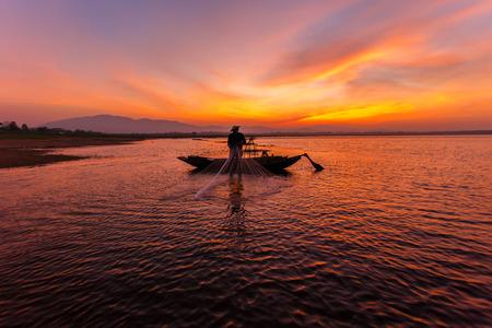 net fishing: Silhouette of traditional fishermen throwing net fishing inle lake at sunrise time, Myanmar Stock Photo