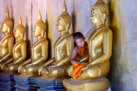 novice: Young Novice monk scrubbing buddha statue at temple in thailand