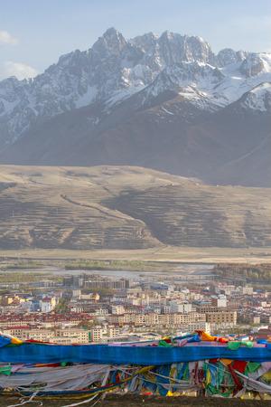 high priest: Village inclose mountain a famous landmark in Ganzi, Sichuan, China
