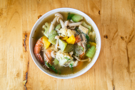 Thai spicy mixed vegetable soup with dried prawn on brown wood table