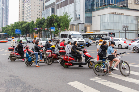 bicyclists: CHENGDU, CHINA - MAY 8, 2016: Bicyclists and bikers on the street in Beijing, China. Bicycles are a common form of transportation in the country.