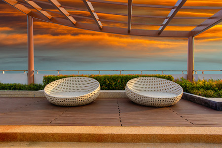 lowboard: Relax corner on condominium rooftop garden with chairs on red sky sunset background