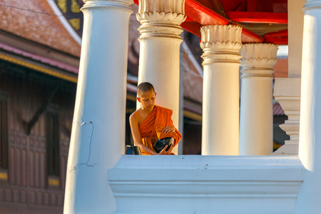 alms: Young Novice monks sit cleaning alms bowl in monastery the big window temple at Ayutthaya historical park in Thailand