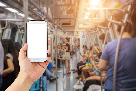 Female hand holding mobile smartphone , tablet, cell phone over Blurred abstract background of people on the Transit train in Singapore